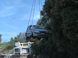Crane lifts car accidentally driven off cliff in Malabar