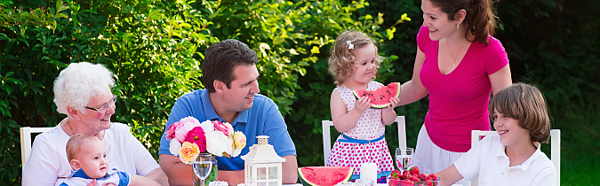 Photo of a family eating fruit at a table outdoors.