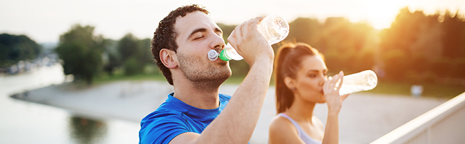 Couple drinking water after evening run