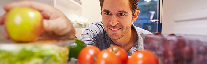 Photo of a man reaching into the refrigerator for an apple.