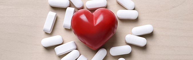 Vitamins and supplements surrounding a red heart