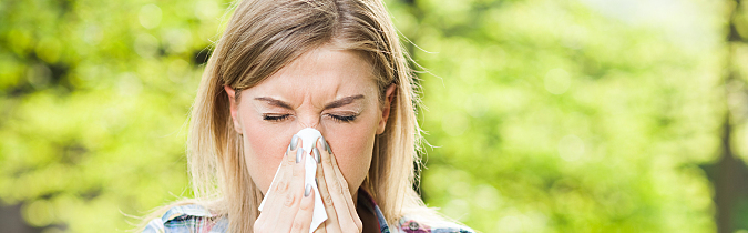 Woman sneezing while outside