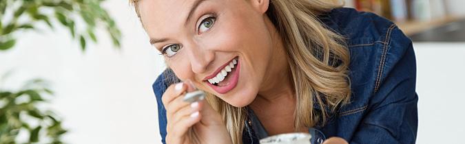 A smiling blonde woman in a denim shirt enjoys a jar of yogurt in her kitchen.