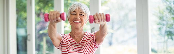 A senior woman lifting weights at the gym