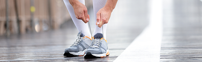 A man wearing compression socks tying his shoes