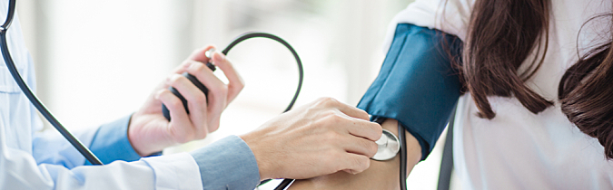 A health care professional performs a blood pressure test.