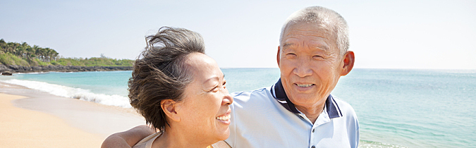 Photo of a couple walking happily along a beach