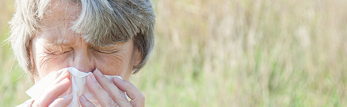 Photo of an older woman sneezing into a tissue.