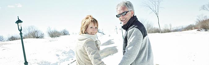 Older couple walking on a snowy street.