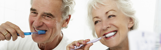 Older couple brushing their teeth