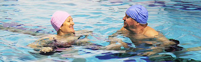 Photo of two older adults swimming together.