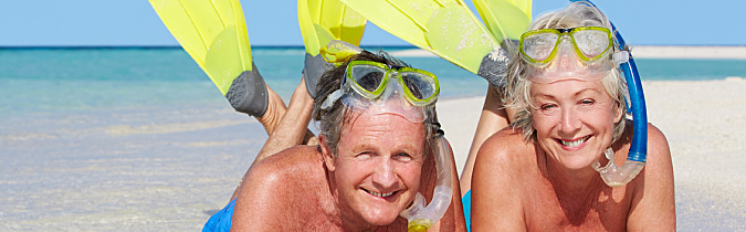 Senior couple on beach with snorkels.