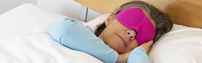 Photo of an older woman sleeping in a sleep mask
