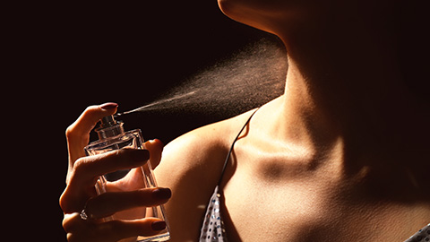 image of woman putting on perfume