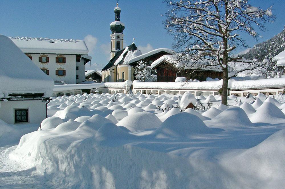 Blick auf den verschneiten Friedhof und die Pfarrkirche St. Pankratius in Reit im Winkl