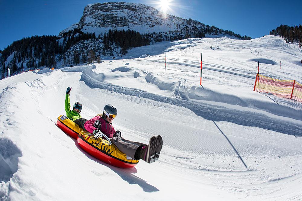 Familie beim Snowtubing mit der Gerlossteinwand im Hintergrund