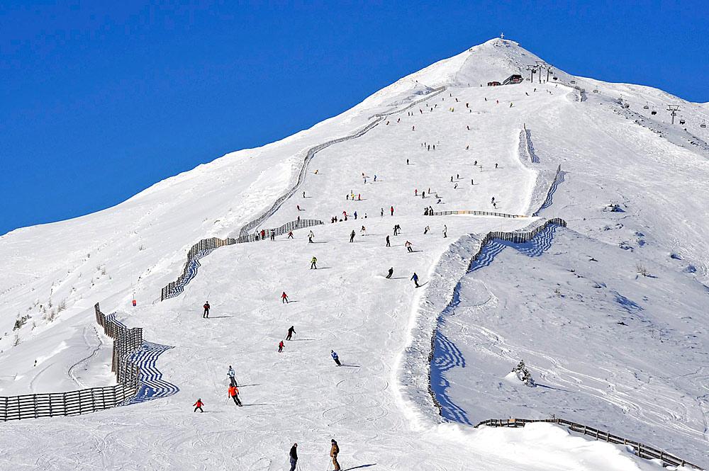 Skifahrer auf einer Piste im Skigebiet Großeck-Speiereck