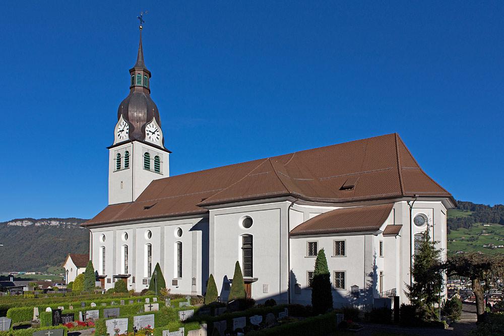 Außenansicht der Pfarrkirche St. Martin mit angrenzendem Friedhof in Buochs