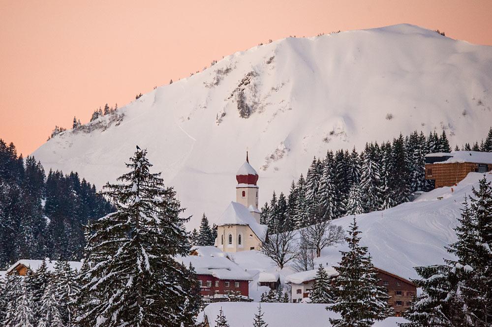 Blick auf die verschneite Pfarrkirche St. Nikolaus im Ortskern von Damüls