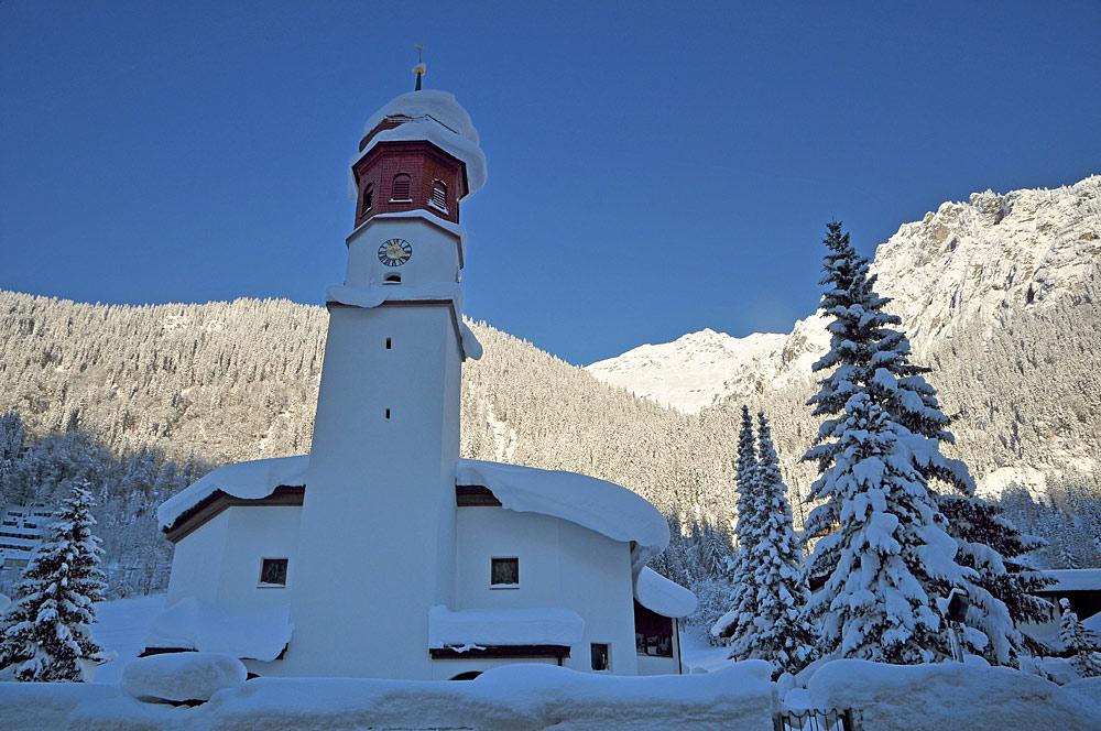 Außenansicht der verschneiten Pfarrkirche St. Johannes der Täufer in Klösterle am Arlberg