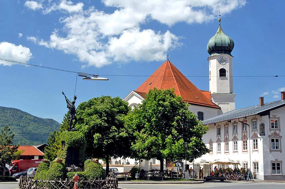 Blick auf Pfarrkirche St. Clemens und Kriegerdenkmal in Eschenlohe