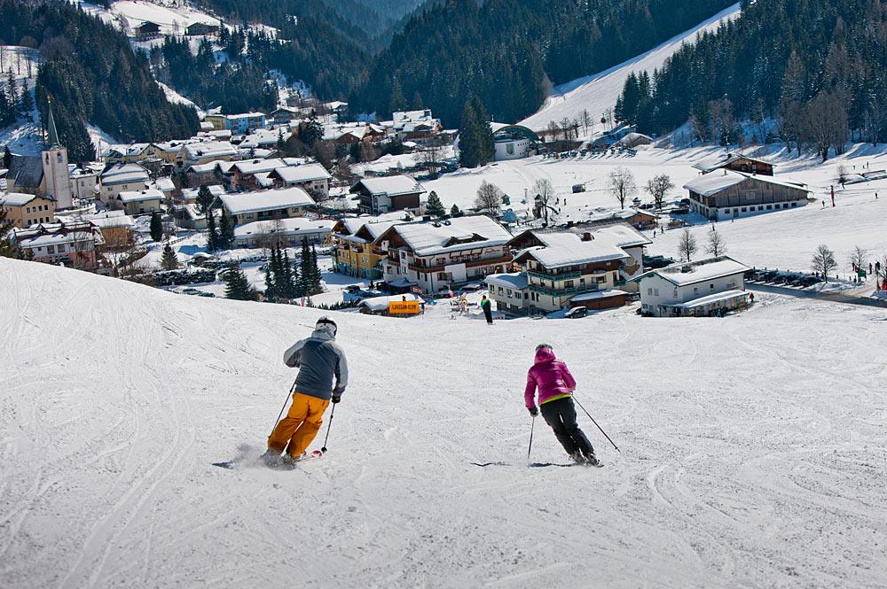 Skifahrer bei der Abfahrt in Filzmoos mit Blick auf den Ort