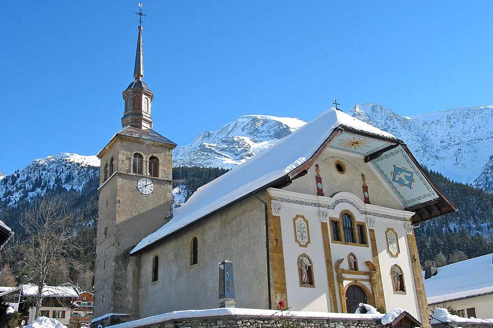 Außenansicht der verschneiten Pfarrkirche Sainte-Trinité in Les Contamines Montjoie