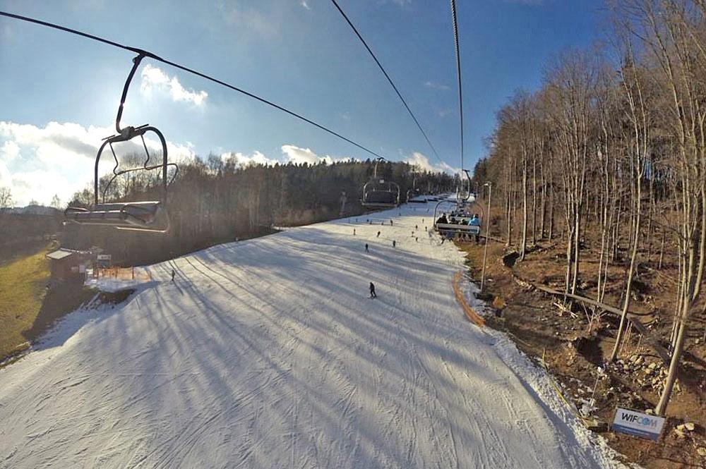 Luftaufnahme des Sessellifts und einer Kunstschneepiste im Skigebiet Moninec
