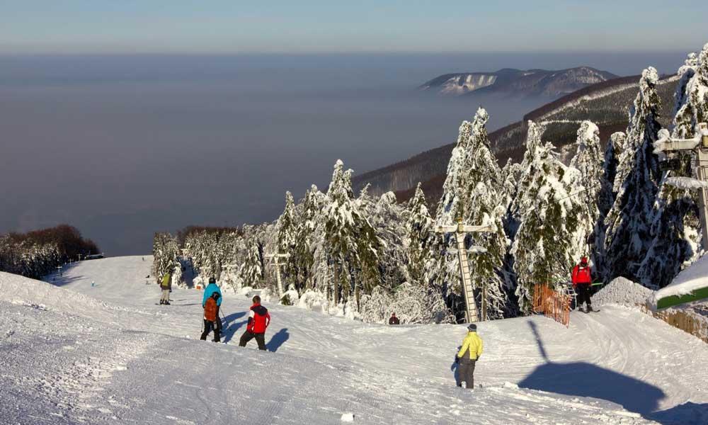Skifahrer auf einer Piste im Skigebiet Pustevny