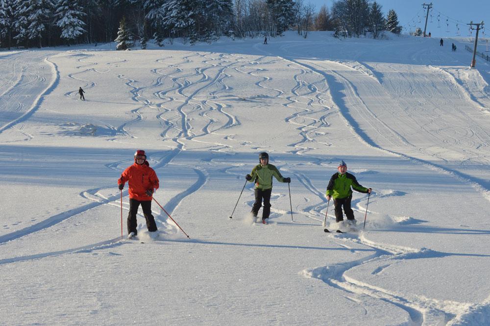 Drei Skifahrer auf der Tiefschneepiste in Geising