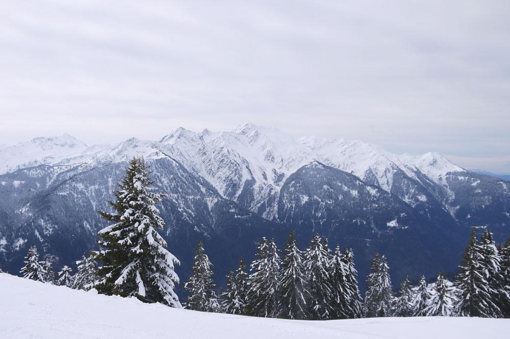 Blick von der Piste in Espace Diamant auf die beschneiten Berge