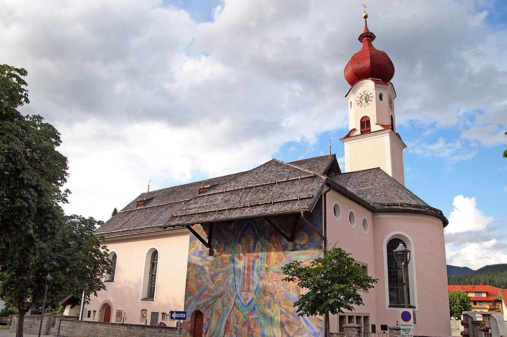 Außenansicht der Pfarrkirche Mariä Heimsuchung mit Wandmalerei in Ehrwald