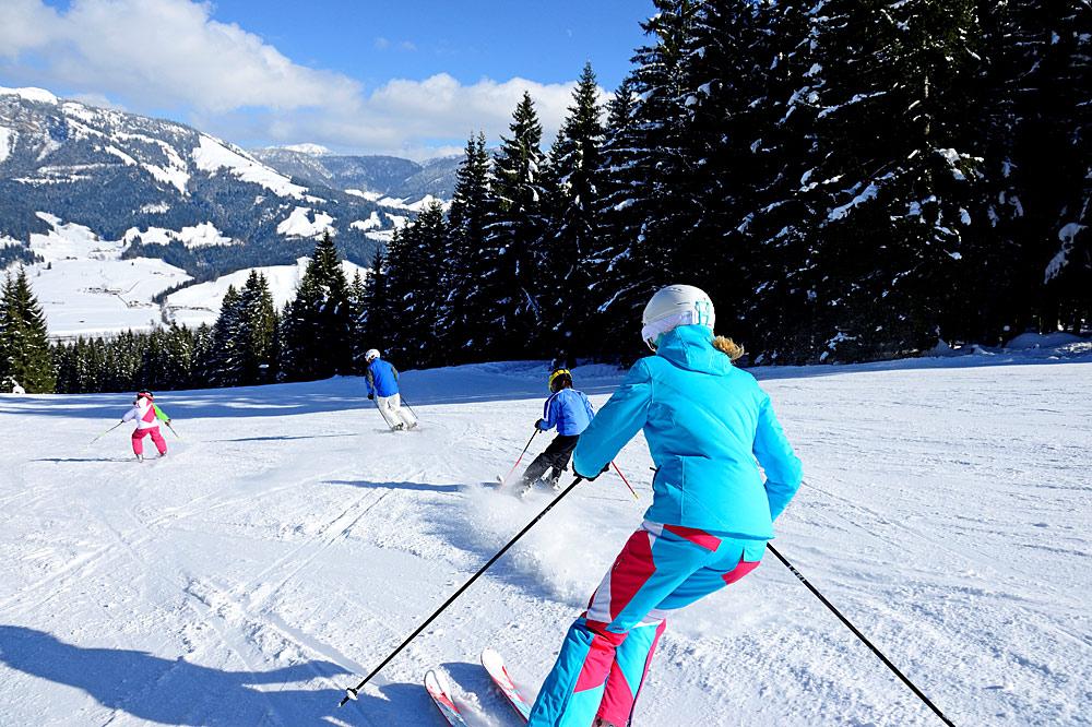 Familie beim Skifahren im Skigebiet St. Johann in Tirol