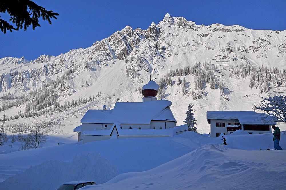 Außenansicht der verschneiten Pfarrkirche Unserer Lieben Frau Mariä Geburt in Stuben am Arlberg