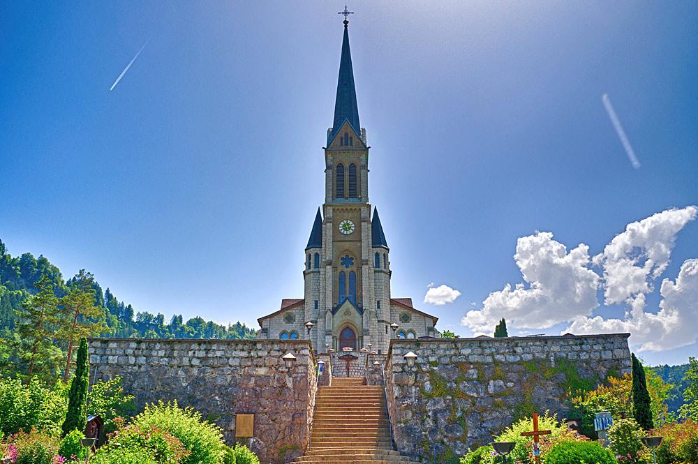 Blick auf die Pfarrkirche Herz Jesu mit der terrassierten Friedhofsanlage in Lungern