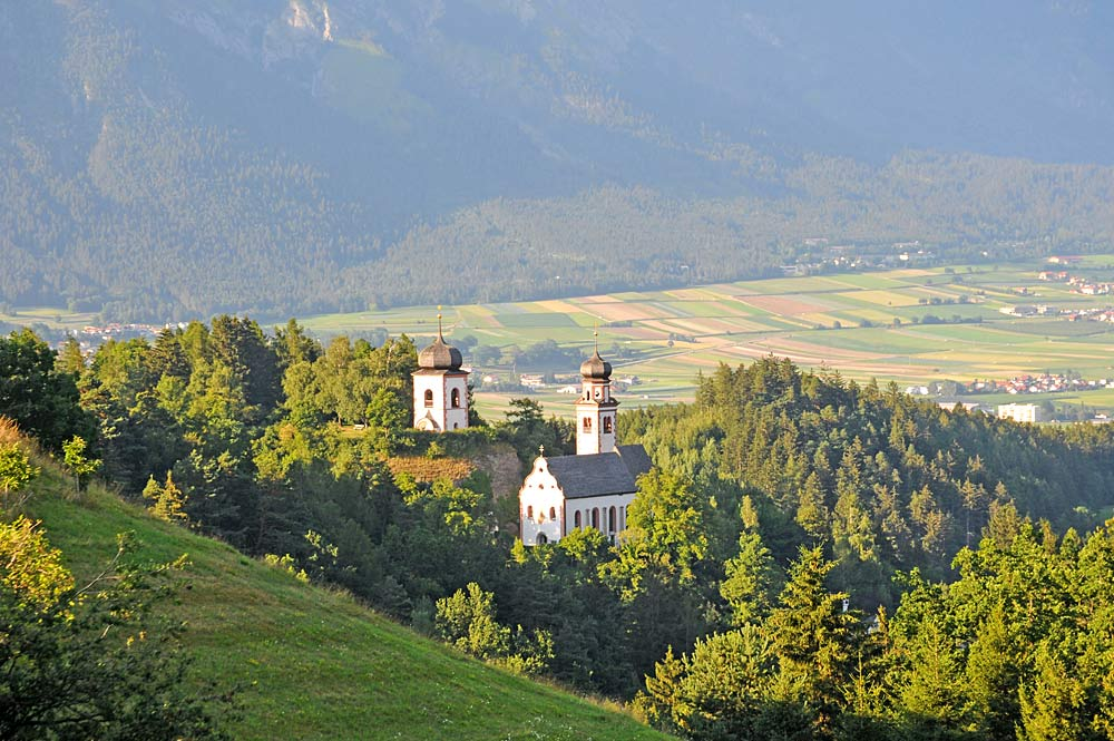 Blick auf die von Bäumen umgebene Pfarrkirche Johannes der Täufer in Ampass