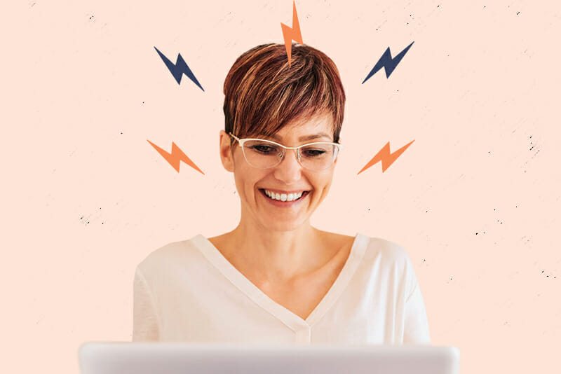 5 Great Tech Jobs for Creative Types - Image of a woman at a computer with lightning bolts around her face