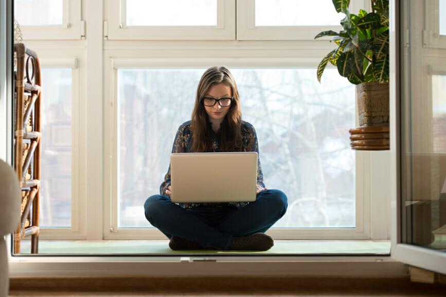 Woman sitting lotus pose laptop floor home
