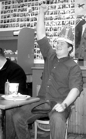 """IAN D. WALKER '03 celebrates his victory after eating six pounds of meat in the """"Burger Pot"""" yesterday."""