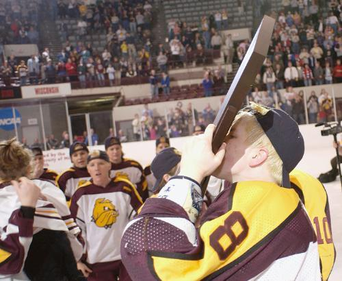 Duluth's ERIKA HOLST, who assisted on the game-winner, kisses the NCAA title plaque.