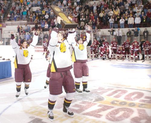 Minnesota-Duluth captain MARIA ROOTH holds the NCAA championship trophy high as the Harvard players watch dejectedly.