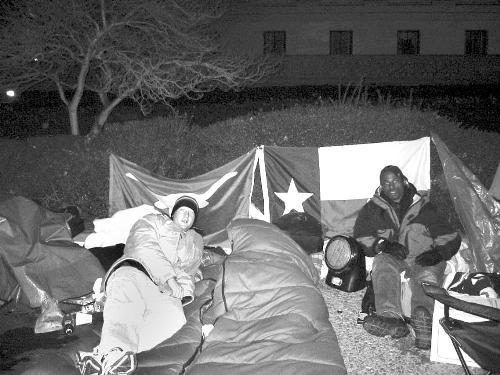 Kennedy School of Government students ADAN D. BRIONES (left), and DARON K. ROBERTS (right) camp out outside the Supreme Court building to get seats for oral arguments of the affirmative action case.