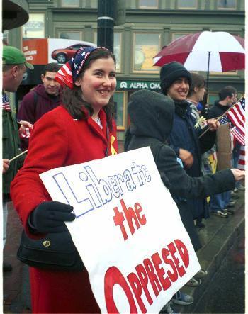 Despite freezing rain, Harvard Divinity School student BRONWEN C. MCSHEA '02 rallies for patriotism Saturday along with a dozen other Harvard students in Harvard Square.