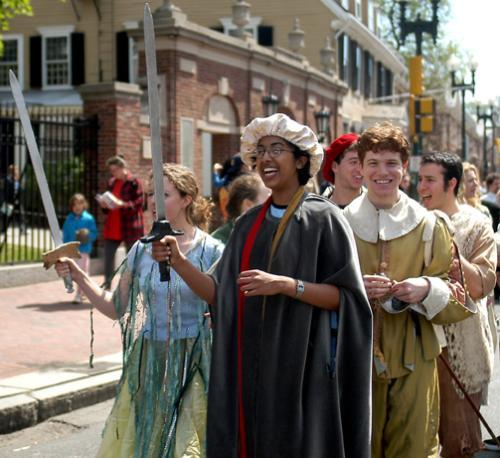 Participants in Harvard's drama programs, wielding swords, march through Mass. Ave as part of the Arts First parade Saturday.
