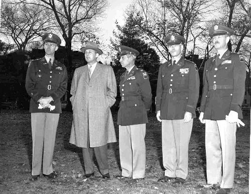 University President NATHAN M. PUSEY '28 stands with military experts and army colonels before a Reserve Officer Training Corps parade in November 1953.