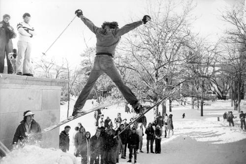 A student demonstrates his skiing skills on a freshly constructed ski jump on the steps of Widener Library as Tercentenary Theater observers look on admiringly.