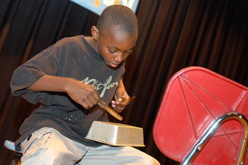 KEITH BROOKS, a student at Summerbridge Cambridge, performs on pots and pans. Several Harvard students and others offer instructions to local middle schoolers through the program. See story, page 3.
