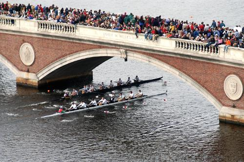 A view from the Dunster House belltower shows a packed Weekes Footbridge as two boats go neck-and-neck on the Charles River during the Head of the Charles Regatta yesterday.