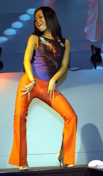 """PAULINE NGUYEN sports her stylish pants and tank-top ensemble at Women in Color's """"Haute"""" fashion show Friday night."""