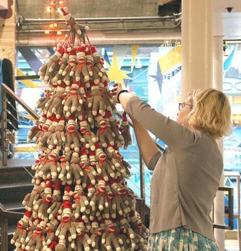 An employee at Urban Outfitters hangs stuffed monkeys on a makeshift Christmas tree in preparation for the holiday shopping season. Square businesses foresee brisk holiday sales as the economy climbs.